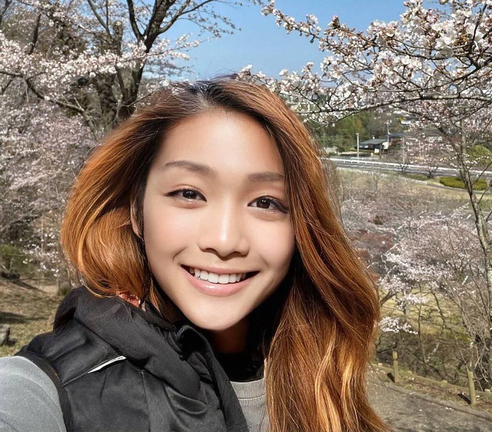 azusaga kuyuki souriante et entourée de fleurs